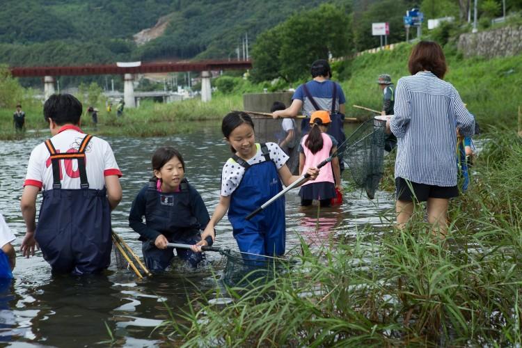지난 7월, 중앙내수면연구소 탐방 후 지구사랑탐사대 대원들이 조종천에서 민물고기 현장교육을 진행하고 있는 모습. - AZA studio 제공 제공